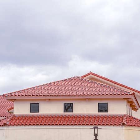 Cadre carré Toit de tuiles rouges sur un bâtiment avec des fenêtres de ventilation sous un ciel gris nuageux