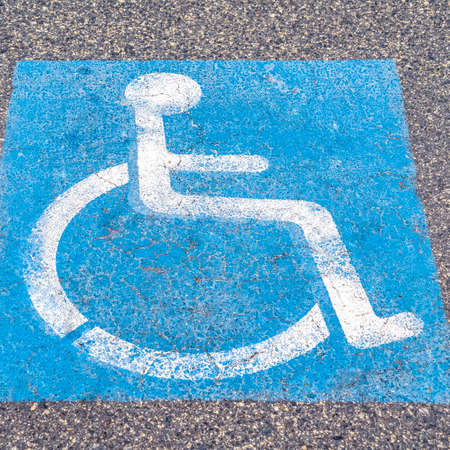Square Disabled or Handicapped road sign painted on asphalt in a restricted area for wheelchair access Stock Photo