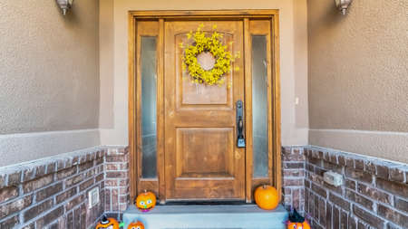Panorama frame Halloween decorations at the door of a house with a colorful floral wreath and jack-o-lantern pumpkins