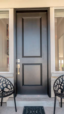 Vertical Two black chairs flanking an entrance door with glass panes to a house in neutral white and grey decor