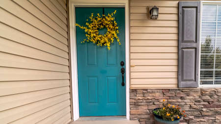 Panorama frame Wooden blue entrance door with floral wreath on a small covered porch of an urban house Stock Photo