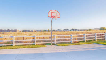 Panorama Empty all weather exterior basketball court surrounded by white picket fence in a rural landscape