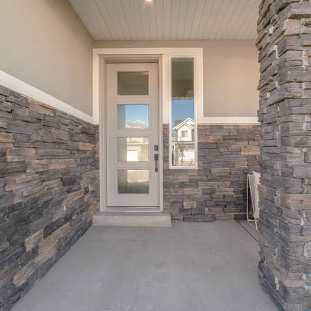 Square frame Glass entrance door to a modern home with covered patio and feature brick wall Stock Photo