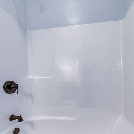 Square Modern interior fitted white tiled shower cubicle with deep tub and mixer taps in closeup