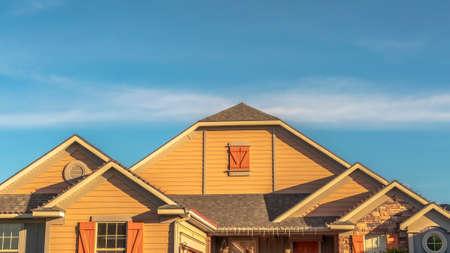 Panorama exterior de la casa con vista del techo a dos aguas con ventanas a dos aguas contra el cielo azul. Diseño de techo arquitectónico de una casa con porche delantero. Foto de archivo