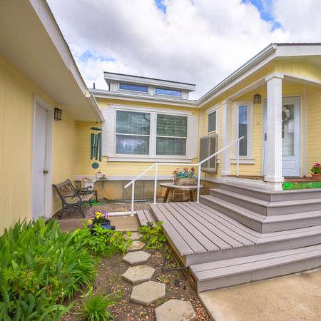 Vierkant frame Stoelen en tafel bij de betonnen veranda van een huis met erkers aan de gevel. De woning heeft ook een glazen deur voor de wit houten voordeur.