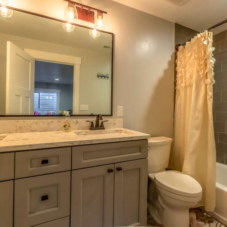 Square Bathroom with vanity and toilet against white wall and bathtub against tile wall. Two sinks are installed on the marble countertop with light bulbs over the mirror. Stock Photo