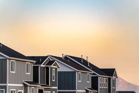 Grey timber clad houses on a housing estate against a colorful orange sky at sunset in close up Stockfoto