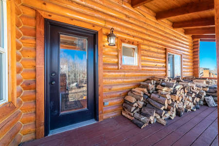 Log cabin with stacked firewood on the porch outside a glass panel front door Stockfoto