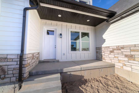 Entrance door to a white timber clad home with small covered porch and sandy yard