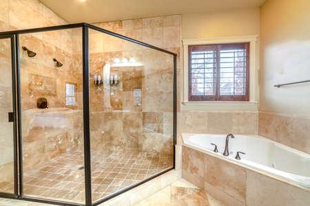 Nowoczesna luksusowa łazienka ze szklaną kabiną prysznicową, dopasowaną narożną wanną i beżowymi płytkami trawertynowymi