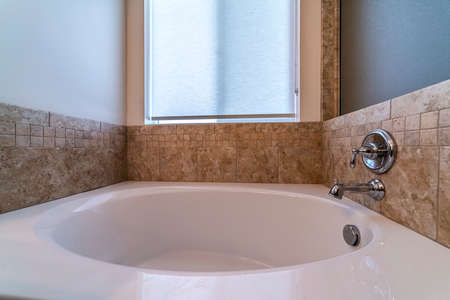 Kleine Badewanne mit Mischbatterie an einer beige gefliesten Wand unter einem mattierten Fenster