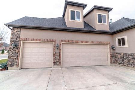 Casa urbana con garage singolo e doppio con vialetto in cemento in primo piano