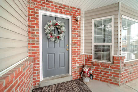 Christmas decorations on a front door of a home with traditional wreath and colorful snowman on the floor