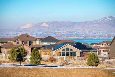 Houses in the Utah Valley with remnants of winter snow on the ground and view to Utah Lake and mountains