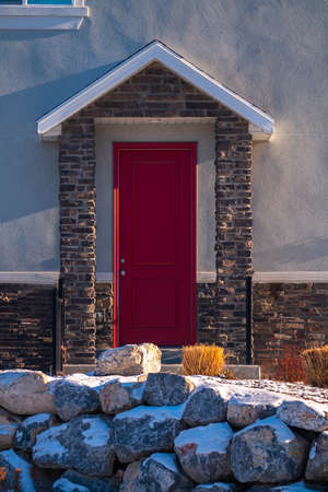 Bright red covered entrance door to a home viewed over a rock wall with winter snow in close up