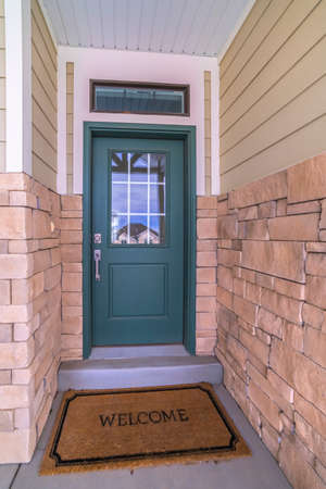 Narrow front entrance in a brick and timber wall leading to a green front door of an urban house
