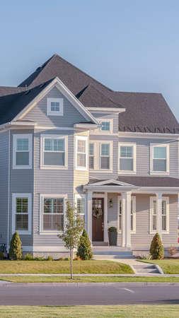 Vertikale Straßenansicht eines modernen grauen zweistöckigen Wohnhauses in einer Wohnsiedlung mit Doppelgarage Standard-Bild