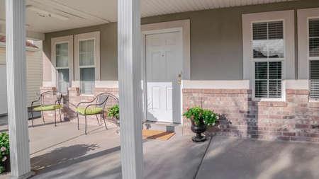 Cornice panoramica Veranda coperta con sedie e porta d'ingresso su una casa urbana con piante in vaso a foglia verde Archivio Fotografico