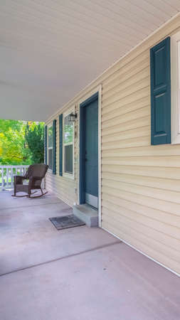 Vertical Long covered veranda in front of a timber house with blue shutters and door with a rocking chair at the far end Stock Photo