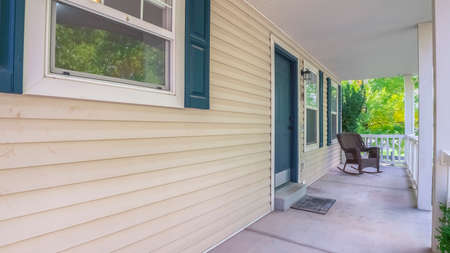 Panorama frame Long covered veranda in front of a timber house with blue shutters and door with a rocking chair at the far end
