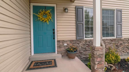 Panorama Colorful blue wooden front door with wreath decoration on a covered porch or passageway of a timber clad house