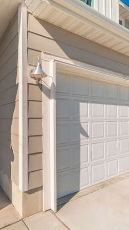 Vertical frame White garage door with recessed covered entrance door alongside in a modern urban house