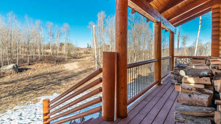 Panorama Wooden porch overlooking winter countryside with snow on the grass and bare branched trees