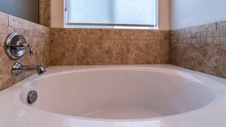Panorama frame Small bathtub with mixer tap on a beige tiled wall below a frosted window
