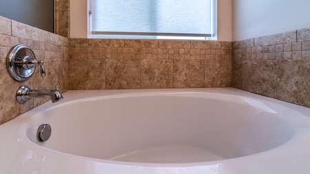 Panoramarahmen Kleine Badewanne mit Mischbatterie an einer beige gefliesten Wand unter einem mattierten Fenster