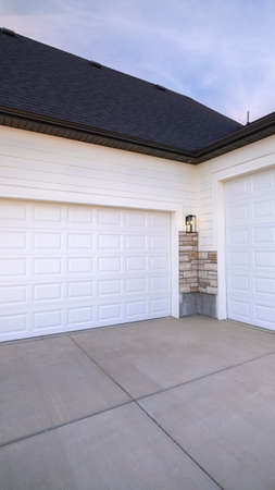 Vertical Two garage doors positioned at right angles sharing a paved forecourt in close up