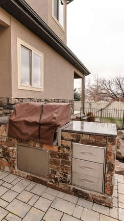 Vertical Covered stone outdoor kitchen on a paved patio