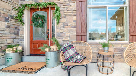 Panorama frame Comfortable wicker chairs on a veranda with decorative green plants and shutters on a large arched window