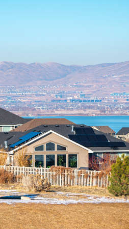 Vertical frame Houses in the Utah Valley with remnants of winter snow on the ground and view to Utah Lake and mountains