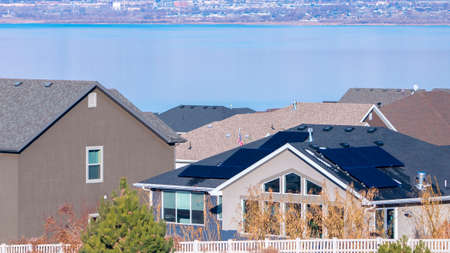 Panorama frame View over rooftops or houses in an estate of the Utah Lake and snow-capped mountains in winter