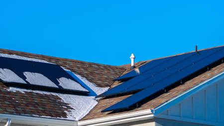 Panorama Frischer Winterschnee und Photovoltaik-Sonnenkollektoren auf einem Dach unter blauem, sonnigem Himmel für grüne erneuerbare Energie und Strom