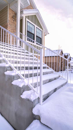 Vertical Cement steps covered in thick fresh snow leading to a covered porch of a building in winter conceptual of the season