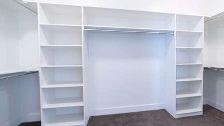 Marco panorámico interior empotrado vacío de un vestidor o armario con estantes y rieles para colgar la ropa