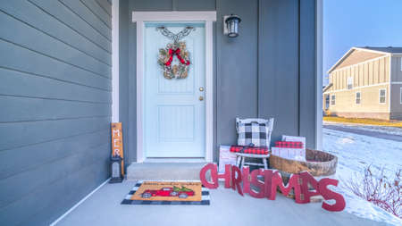 Panorama frame Front porch of a home decorated for Christmas with wreath on the door and decorations on the floor alongside a brightly colored mat with view to snow outside. Stock Photo