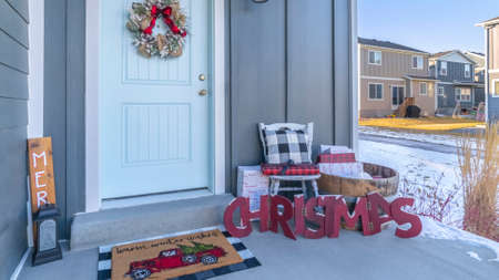 Panorama Christmas decorations and wreath outside the front door of a house on a modern housing estate with winter snow on the ground