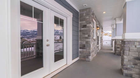 Panorama Reflection of a winter landscape in large glass windows of a modern house looking down the covered porch
