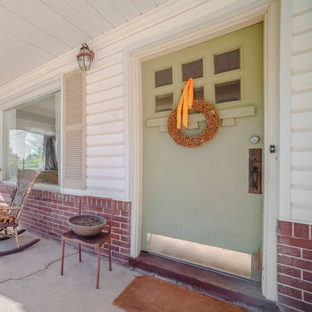 Square Two rocking chairs on a covered front porch alongside a green front door with decorative wreath on an urban house Stock Photo