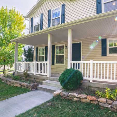 Maison carrée en bois blanc avec volets et véranda avant avec rampe en bois dans des pelouses vertes soignées
