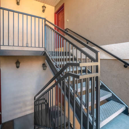 Square frame Interior stairs and landing with bannister rail in an apartment block or office building Stock Photo