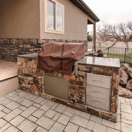 Square Covered stone outdoor kitchen on a paved patio Stok Fotoğraf
