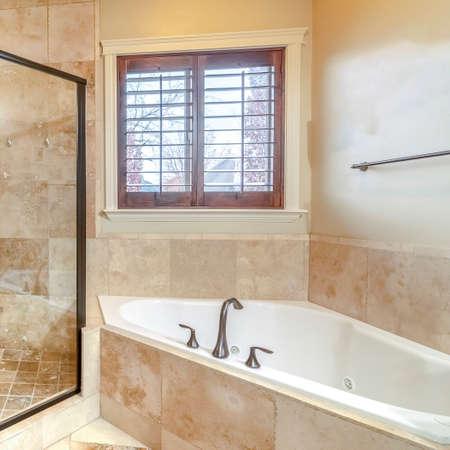 Kwadratowa rama Nowoczesna luksusowa łazienka ze szklaną kabiną prysznicową, dopasowaną narożną wanną i beżowymi płytkami trawertynowymi