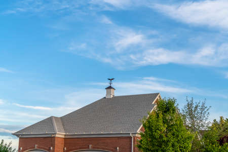 Exterior of building with cupola and compass on the gray pitched roof. The building has red brick wall and cloudy blue sky can be seen in the bakcground.