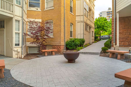 Fire pit on circular patio outside building with white and stone brick wall. Stone benches, pathways, and lush plants can also be seen in this residential landscape. Imagens