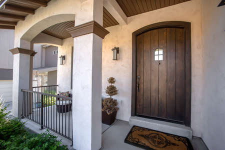 Brown wood arched front door with glass panes at the facade of home with porch. Square columns, railings, chair, plants, wall lamps, and dormat can also be seen at the exterior of this house.