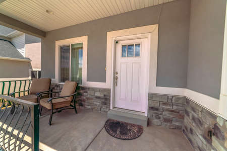 Entrance of home with chairs at the porch and front door with glass panes. Window and security camera can also be seen at the facade of this house.